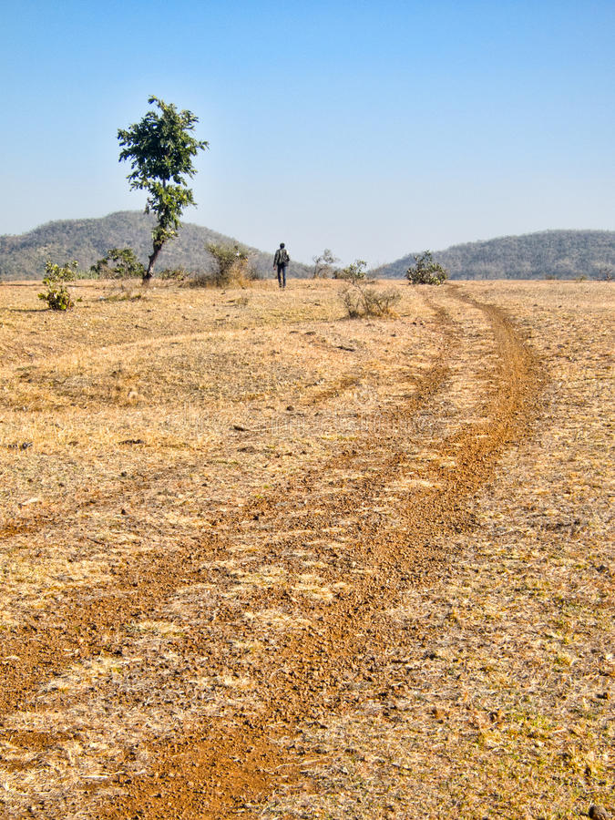 Dusty track in wilderness. Scenic view of tyre tracks on dry landscape with mountain range and solitary person walking in background royalty free stock photo