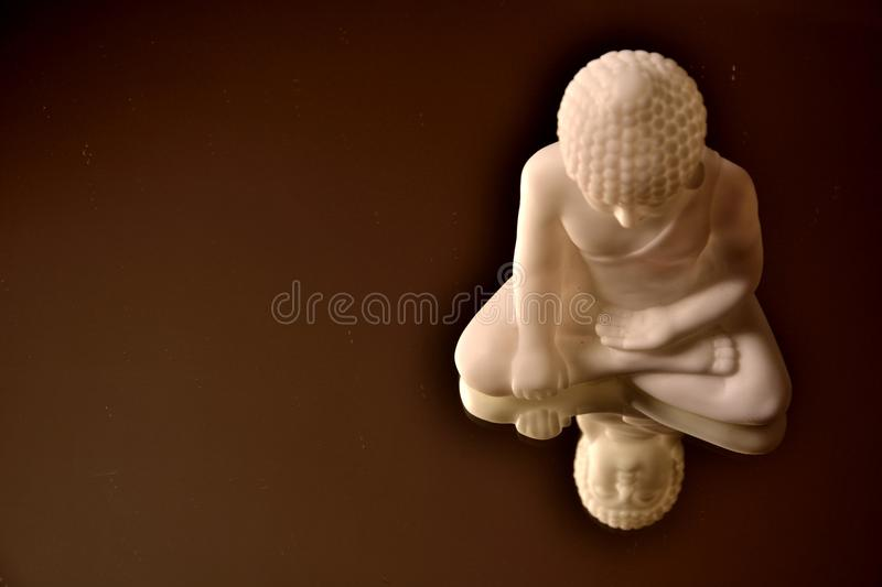 Dusty white buddha. On a brown mirror-like surface stock photos