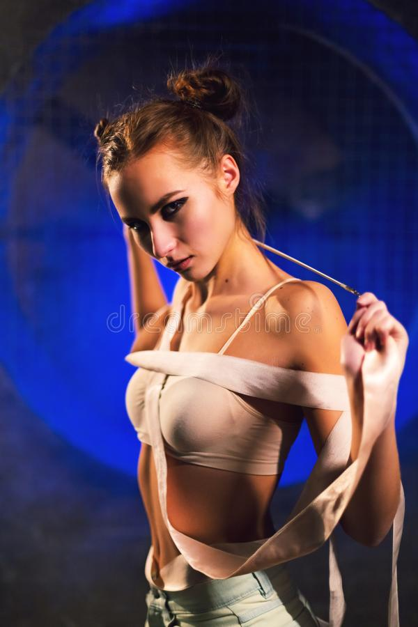 Duszna piękna młoda gimnastyczki kobieta pozuje z gimnastyki taśmą obraz royalty free