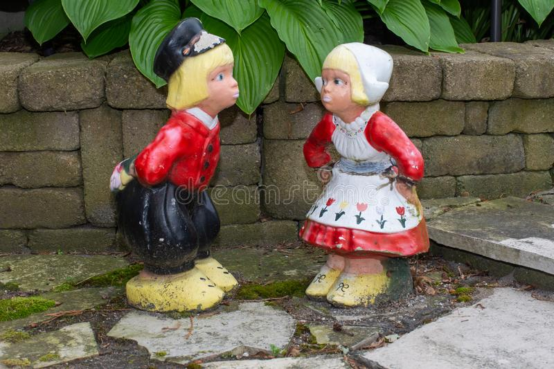 A Dutch boy and girl lawn ornaments standing with wooden shoes and traditional dutch clothes from the Netherlands in Europe stock photo