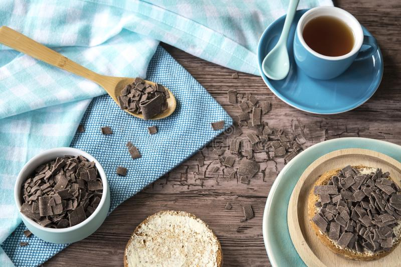 Dutch breakfast with rusk and chocolate flakes, blue mug with tea. Blue cup and saucer with tea, wooden bowl and rusk with Dutch chocolate flakes, on wooden stock photos
