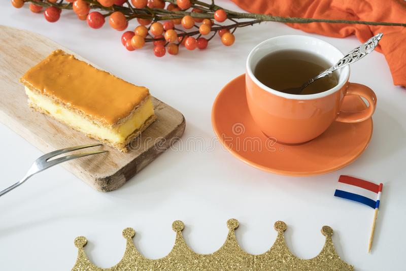 Orange tompouce, traditional Dutch treat with pudding and frosting on national holiday Kings Day April 27th, in The Netherlands. Dutch breakfast setting for stock images