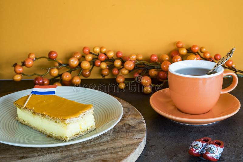 Orange tompouce, traditional Dutch treat with pudding and frosting on national holiday Kings Day April 27th, in The Netherlands. Dutch breakfast setting for stock photography