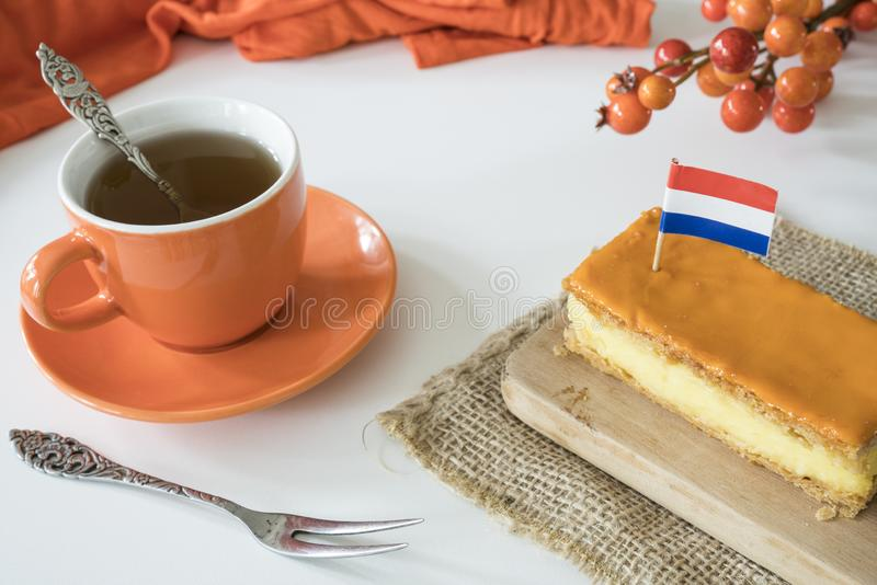 Orange tompouce, traditional Dutch treat with pudding and frosting on national holiday Kings Day April 27th, in The Netherlands. Dutch breakfast setting for royalty free stock image