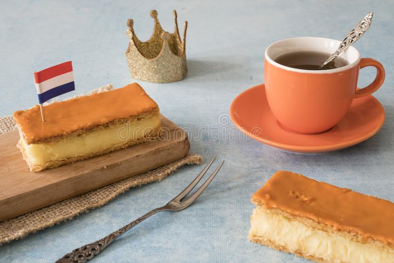 Orange tompouce, trditional Dutch treat with pudding and frosting on national holiday Kings Day April 27th, in The Netherlands. Dutch breakfast setting for royalty free stock photography