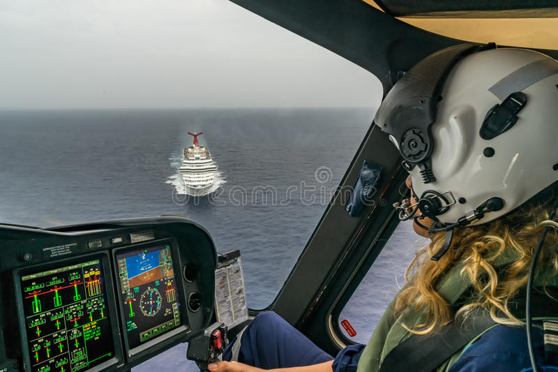 The Dutch Caribbean Coastguard - female pilot over a crusie ship. The Dutch Caribbean Coastguard / Cobham Aviation training with the AW139 helicopter in Curacao royalty free stock images