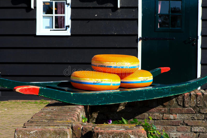 Dutch Cheese wheels on a green cart. With farm house in the background stock photography