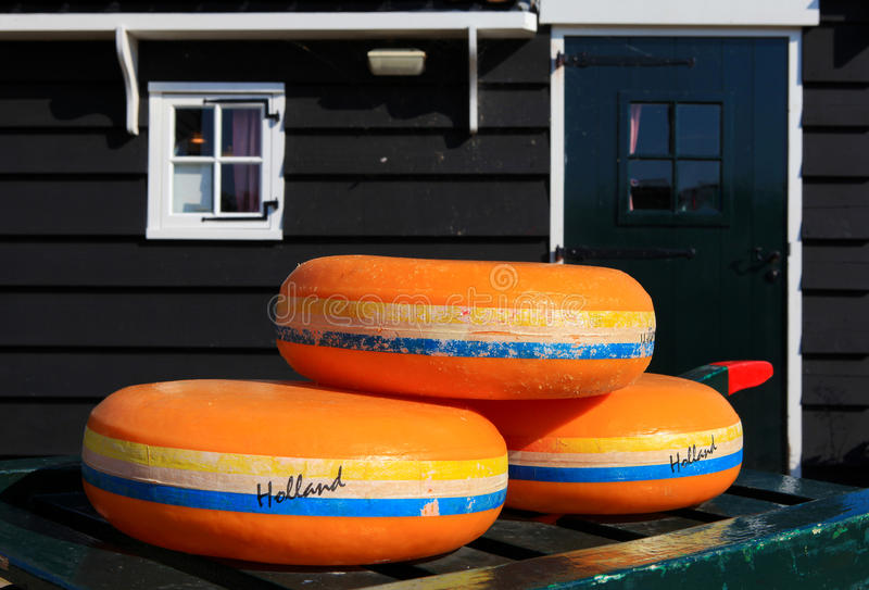 Dutch Cheese wheels on a green cart. With farm house in the background royalty free stock photos