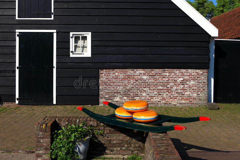 Dutch Cheese wheels on a green cart. With farm house in the background stock images
