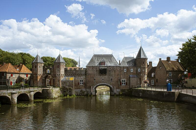Dutch city during summer, Medieval town wall Koppelpoort and the Eem river in Amersfoort, Netherlands. Antique architecture and a bridge. Blue sky with clouds stock photo