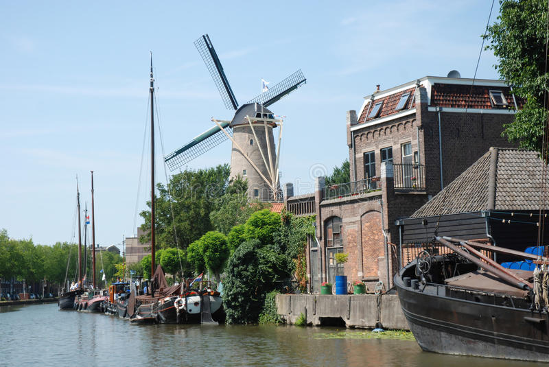 Dutch cityscape Gouda with canal-windmill-ships. Dutch historic cityscapes Gouda, with canal area, windmill De Roode Leeuw, old ships and warehouse stock photo