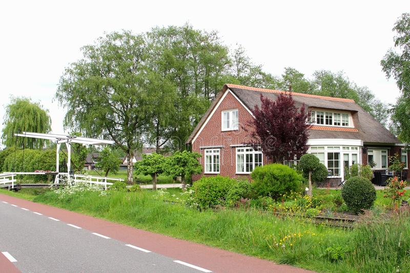 Dutch country house with a garden, canal and a draw-bridge, Netherlands. A big detached country house with garden architecture, a small ditch and a traditional stock images