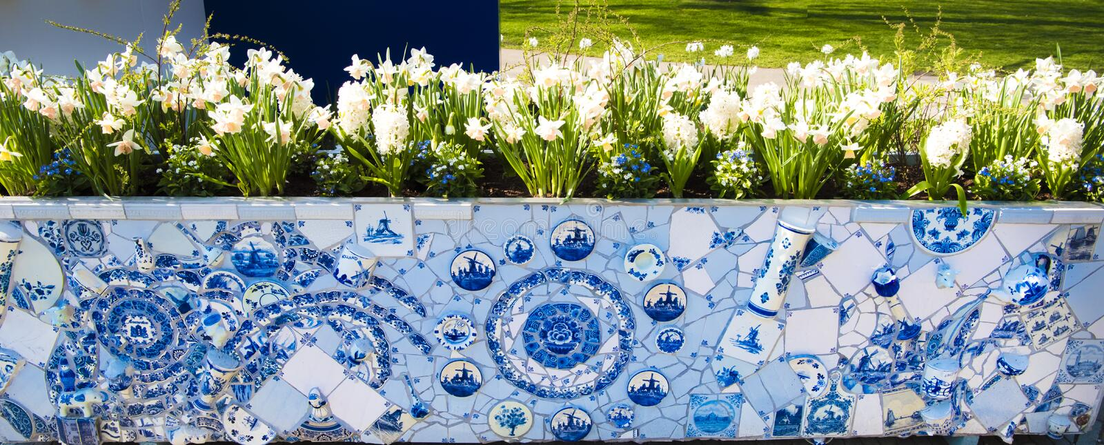Dutch delfter porcelain tiles, vases and pots in new flower tub. Typical dutch blue and white Delft porcelain flower tub with White daffodils stock photos