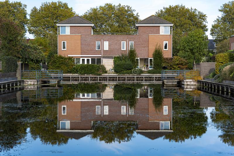 Dutch detached modern houses. Dutch modern detached houses surrounded by trees reflected on the water of a calm canal at an early sunset moment in Voorburg city