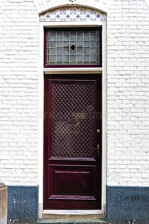 Dutch Door with Glazed Tiles. Entrance door into a building of traditional architecture in Amsterdam, Netherlands. Dutch front door with glazed tiles in a white royalty free stock image