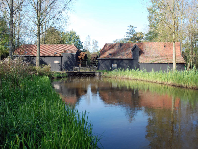 Dutch double water mill mirror in river-Eindhoven. The Coll Watermill - an historic corn and oil mill in the town of Eindhoven-Tongelre - province Noord-Brabant stock photo