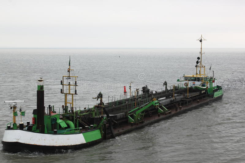 Dutch dredger in in Wadden Sea near Ameland island stock photography