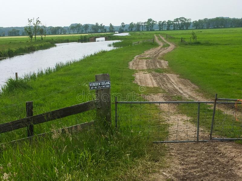Dutch dyke embarkment with wooden fence royalty free stock photography