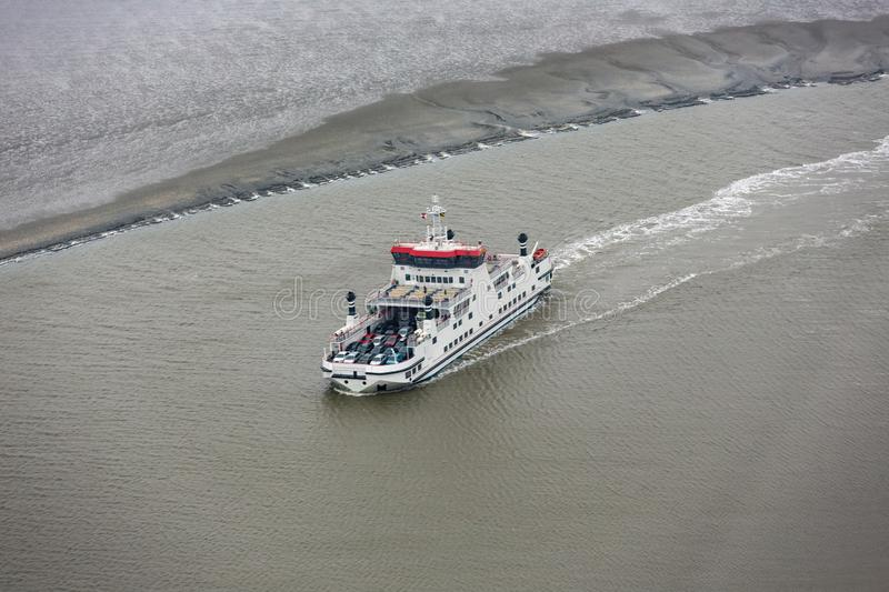 Dutch ferry boat at Wadden Sea navigating beween sandbanks stock photos