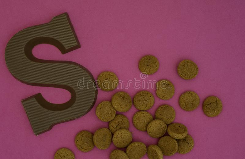 Dutch fest called Sinterklaas image with pepernoten and a cholotale letter. Dutch candy called pepernoten and a chocolate letter on a pink background. For the royalty free stock photos