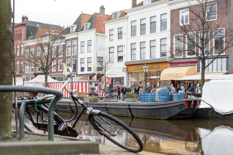 Dutch fresh food market in historic city center of Leiden, with a parked bicycle along the canal stock image