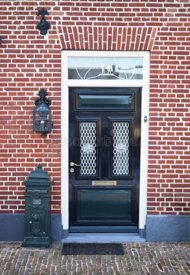 Dutch front door with mailbox and lantern. Brick house. Dutch front door. Green. Brick house old style with old stone street in front stock images