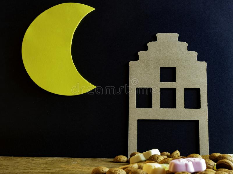 Dutch house from cardboard with candy called pepernoten and schuimpjes for the fest called Sinterklaas. A cresent yellow moon, with candy called pepernoten and stock photography