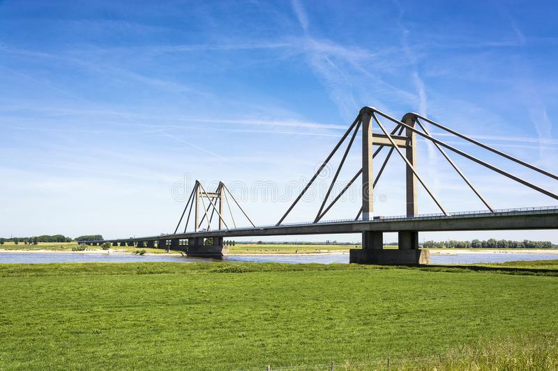 Dutch landscape with bridge over the river Waal in the Netherlands, with blue sky and green meadows royalty free stock photography