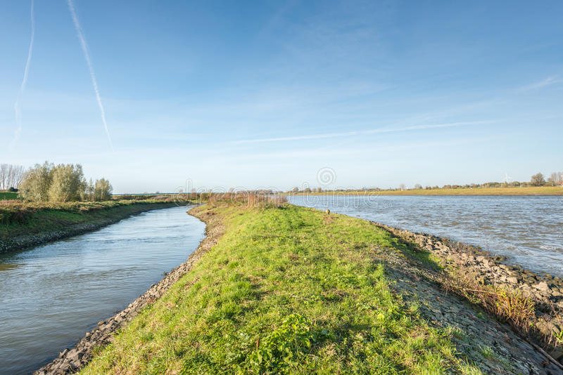 Dutch landscape with water. A dike, a narrow and a broad waterway on a sunny day in the fall season royalty free stock photo