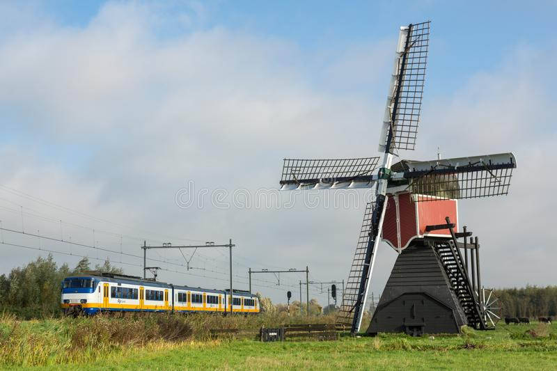 Dutch landscape with windmill and train royalty free stock image