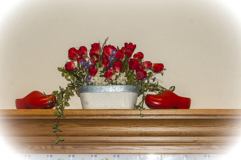 Dutch Mantel. Red tulips and wooden shoes decorating a fireplace mantel royalty free stock image