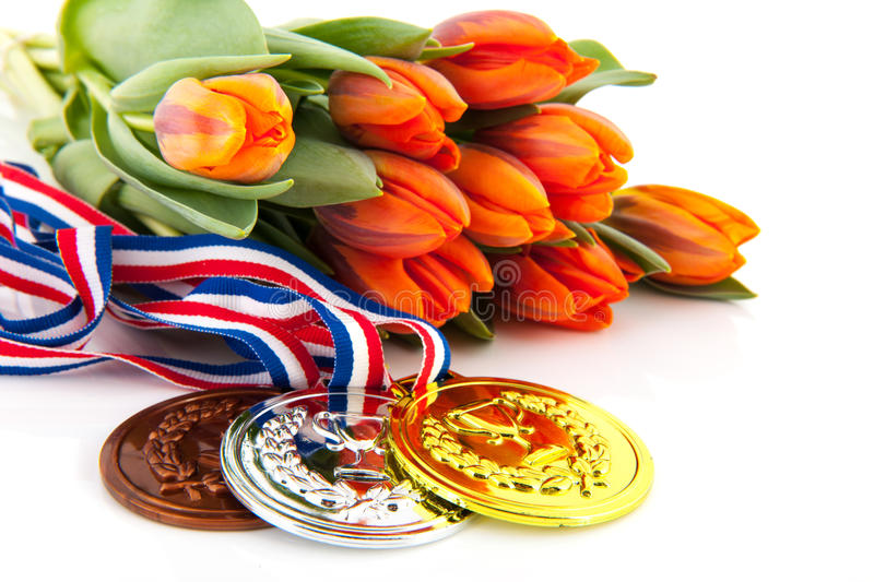 Dutch medals and orange tulips. Dutch medals in gold, silver and bronze in front of orange tulips over white background royalty free stock photos