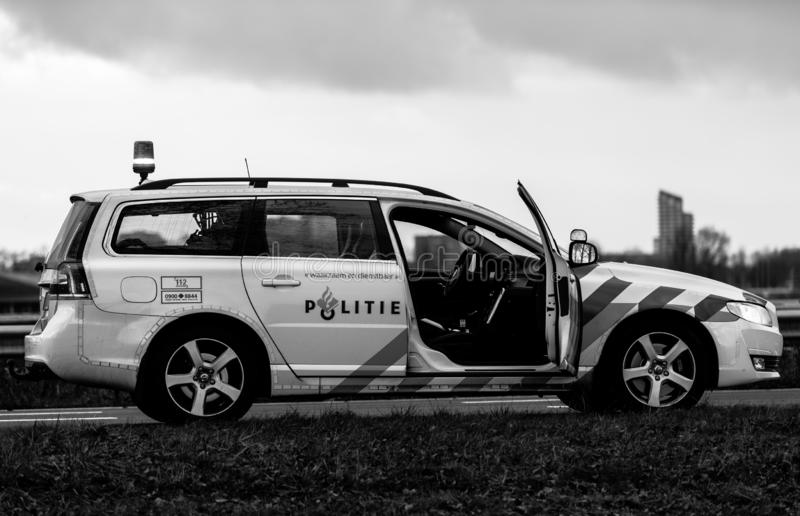 Dutch police car. At accident, door open, Volvo, photo in black and white. Cloudy sky and no sun background stock photo