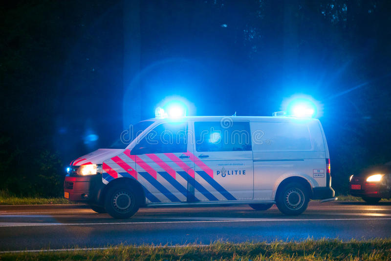 Dutch police car lights. VARSSEVELD, NETHERLANDS - OCT 29, 2015: A Dutch police car with emergency lights holding traffic during a car accident stock image