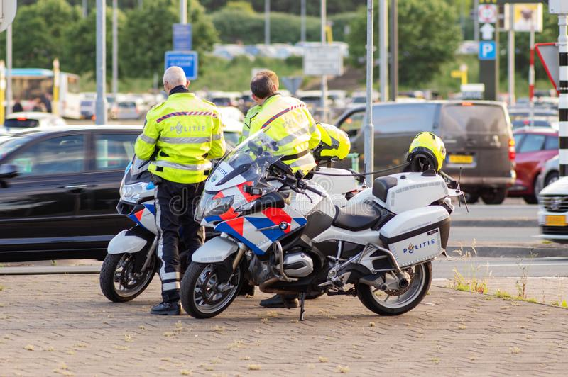 Dutch police officers are standing by their bikes stock photos