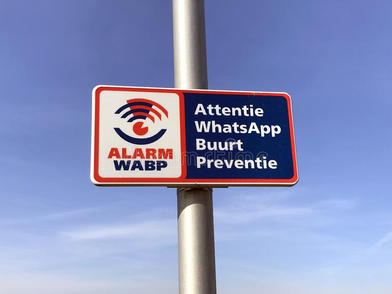 Dutch signpost announcing WhatsApp Neighborhood Prevention Watch. royalty free stock photo