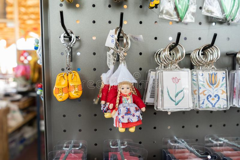 Dutch souvenirs from Holland being sold in a gift shop, with wooden clog keychains, a Dutch milkmaid keychain and flower keychains royalty free stock images