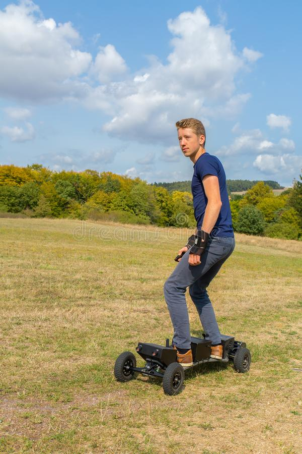 Dutch teenage boy rides electric mountainboard offroad. Young european man rides electrical mountainboard offroad stock photo