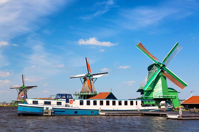 Dutch typical landscape. Traditional old dutch windmills with cruise ship and blue sky in the Zaanse Schans village, Netherlands. stock photography