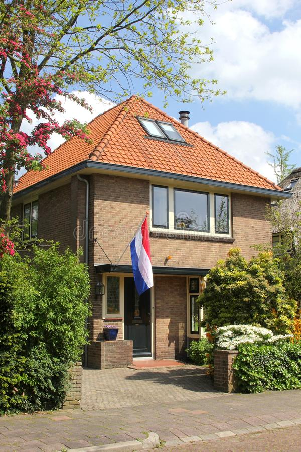 Characteristic Dutch home with the Dutch national flag, Holland royalty free stock images