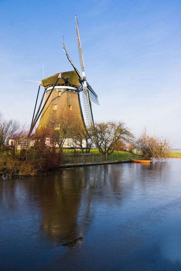 Dutch windmill in frozen polder landscape stock images