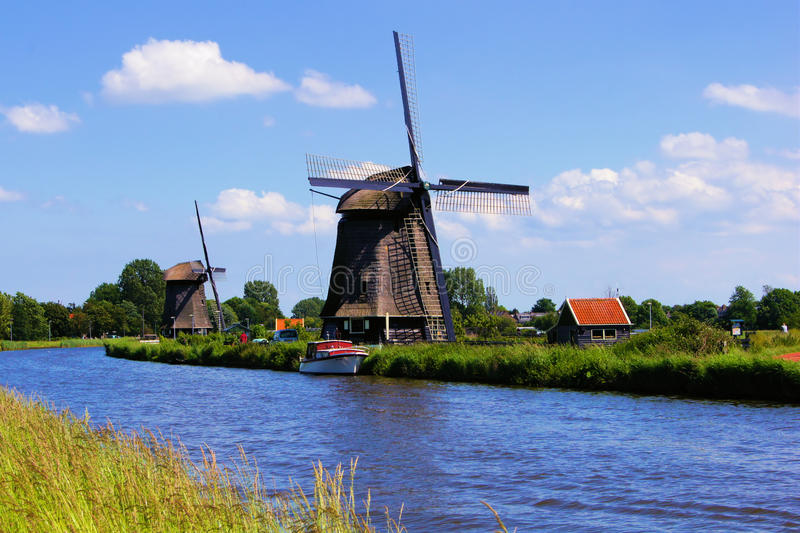 Dutch windmills. View of traditional Dutch windmills along a canal near Alkmaar, The Netherlands royalty free stock photography