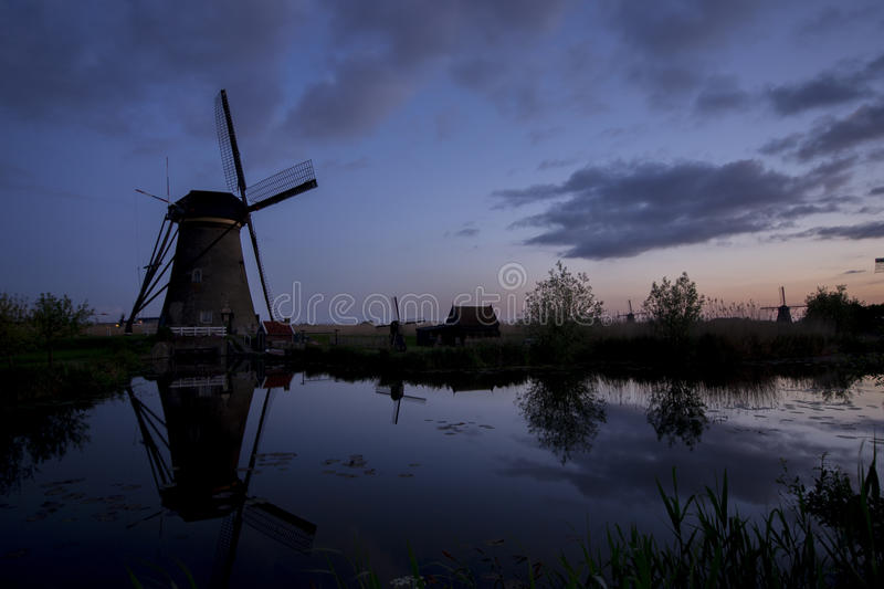 Dutch Windmills II. The sun comes up in Kinderdijk, The Netherlands. See the reflection of the objects in the water royalty free stock photography