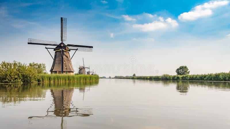 Row of dutch windmills alongside the canal stock photo