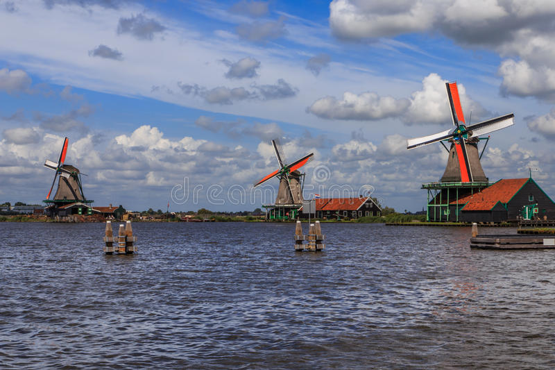 Dutch windmills. Three Dutch windmills near water under typical Dutch skies royalty free stock image