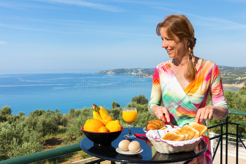 Dutch woman eating breakfast with sea background royalty free stock image