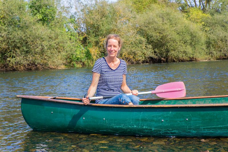 Dutch woman with paddle in canoe on river royalty free stock image