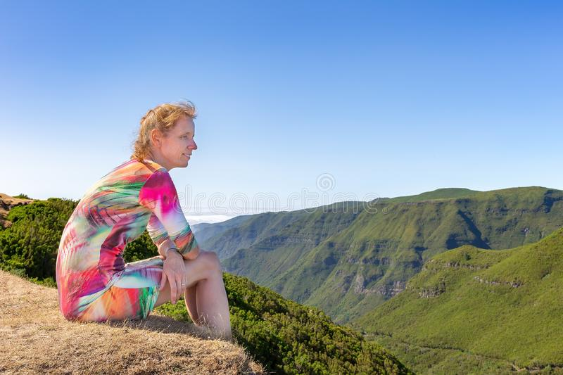 Dutch woman sitting in mountain landscape royalty free stock image