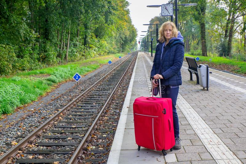 Dutch woman with suitcase stands on train station royalty free stock photo