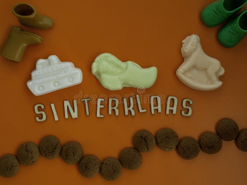Dutch word Sinterklaas Santa Claus with Dutch candy called pepernoten. Dutch candy called schuimpjes and pepernoten on an orange background with the Dutch word royalty free stock photo
